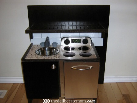 A play kitchen DIY project! We worked to make this kitchen look like our own kitchen. It was inexpensive and was built from the base of a small IKEA end table. Easy, cute, inexpensive and original! Check out these instructions on how to build a build a play kitchen!