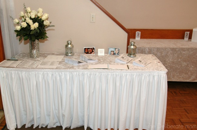 The table at the entrance of the hall has wedding photos of the bride and groom's parents.
