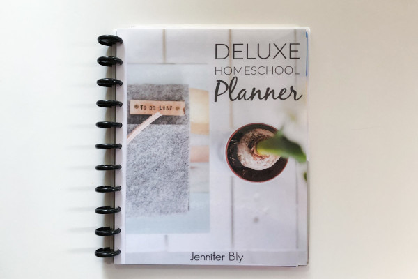 Disc bound homeschool planner on a white table
