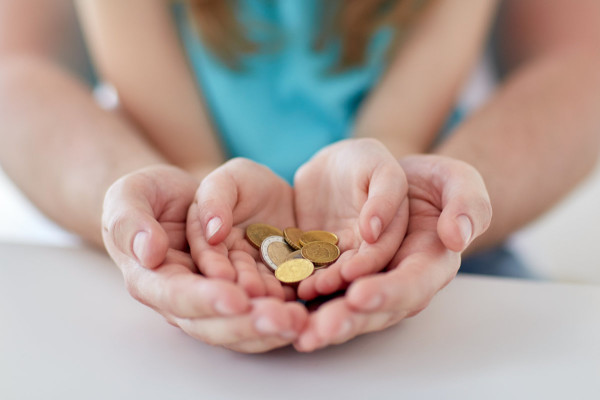 Parent cupping child's hands full of coins