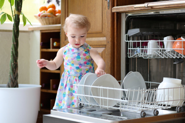 A young toddler in a multicoloured polka-dot dress putting dishes into the dishwasher